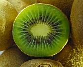 Half a kiwi fruit among whole fruits (close-up)