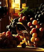 Basket of black & green grapes, glass of red wine in background