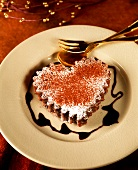 Heart-shaped chocolate cake with chocolate sauce on plate