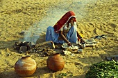 Woman sitting on ground cooking food (Rajasthan, India)
