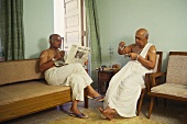 Two S. Indian men in white lungis drinking coffee