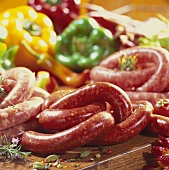 Various types of raw sausages, peppers behind