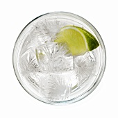 A glass of water with lime and ice cubes
