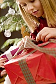Girl untying ribbon on a Christmas parcel