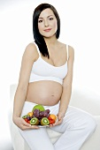Pregnant woman seated, holding plate of fruit in her hand