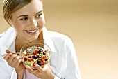 Young woman holding bowl of fruit muesli and spoon