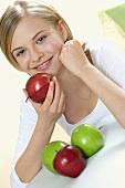 Junge Frau mit vier Äpfeln, den Kopf auf Arm aufgestützt