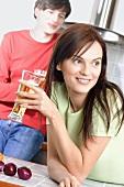 Junge Frau mit Bierglas in der Küche, Mann im Hintergrund