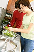 Young couple in kitchen washing lettuce