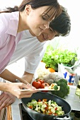 Young couple frying vegetables in wok