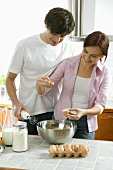 Young couple baking, woman separating egg into a bowl