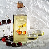 A bottle and two glasses of kirsch (cherry brandy)