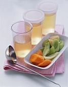 Gemüsebrühe in Gläsern und eine Schale voll Suppengemüse