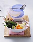 Fish broth & bowl of ingredients (fish, vegetables & herbs)