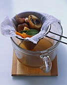 Conical sieve of soup vegetables over clear vegetable broth