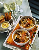 Two dishes of fish soup on tray