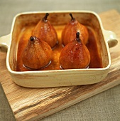 Four baked pears with honey in baking dish