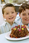 Two boys sitting in front of birthday cake