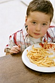 Boy sitting in front of plate of chips