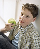 Boy holding apple with a bite taken