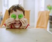 Boy holding green coiled jelly sweets in front of his eyes