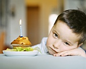 Small boy sitting sadly beside muffin with birthday candle