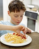 Boy dipping chips into ketchup