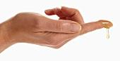 Honig tropft vom Finger einer Frauenhand
