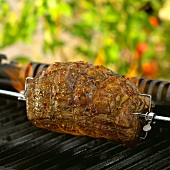 Rolled beef joint on grill spit over barbecue