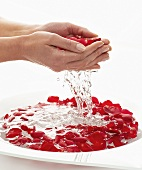 Water falling out of hands full of rose petals