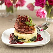 Thin slices of duck on vegetable puree with cranberries
