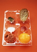Plastikbehälter mit Corned Beef, Eigelb, Tabasco und Brot