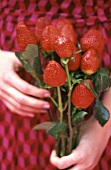 Woman holding bouquet of strawberry 'roses'