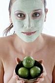 Frau mit Gesichtsmaske hält drei Limetten