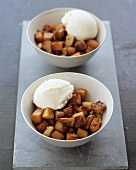 Two dishes of toasted diced pumpkin and vanilla ice cream