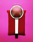 Tea strainer and kitchen sponge on violet background
