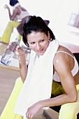 Junge Frau mit Handtuch um Hals hält eine Wasserflasche