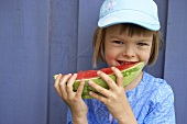 Girl with slice of melon in her mouth in front of blue wall