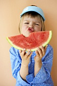 Girl holding slice of melon with a bite taken
