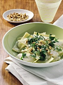 Ravioli in herb cheese sauce with rocket and pine nuts