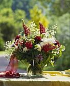Rote Lupinen mit weissen Hortensien