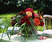 Rustic bouquet of roses with grasses on laid table