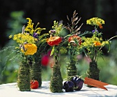 Zinnias in vases wrapped in moss, with label