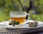 Sage tea in glass cup with coconut chocolates & sage leaves