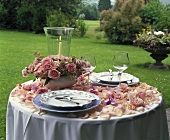 Romantic table with rose petals, arrangement of roses in garden