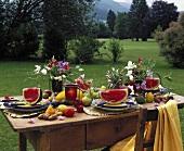 Sommerlich gedeckter Tisch mit Melonen, Früchten und Blumen