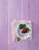 Strawberry with leaf in a white bowl