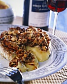 Hot Camembert with nuts, glass of red wine in background