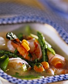 Vegetable broth with green asparagus and shrimps
