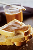 Three slices of toast, one spread with honey, a bite taken